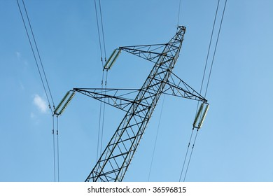 High voltage electricity pillar against clear blue sky