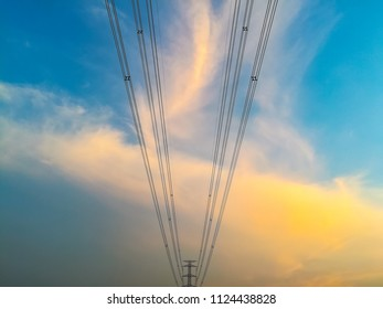 High voltage electricity post structure and wire line with beautiful lighting and cloud above the blue sky