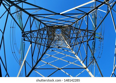 High voltage electricity pylon from the ground up against blue sky