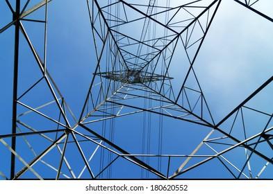 High voltage electricity pylon on bright sky.
