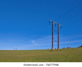 High voltage electricity pylons on a field against blue sky.