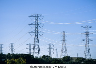 High voltage electricity towers on a blue sky background, San Francisco bay area, California
