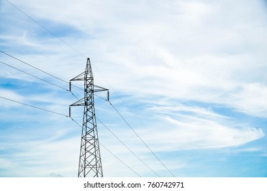 high voltage electricity transmission pole with blue sky at noon. energy is sent by high voltage cable.