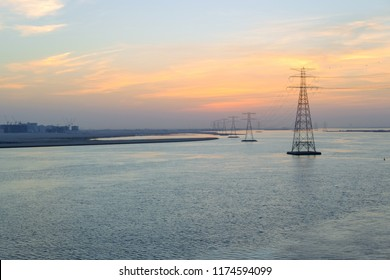 High voltage Electricty Power lines distributed through Ocean with amazing colourful clouds in background, Abu Dhabi, UAE