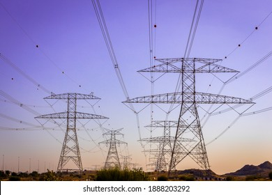 High voltage eletrical towers and lines, symmetrical view with purple sky in the background, Dubai, United Arab Emirates.