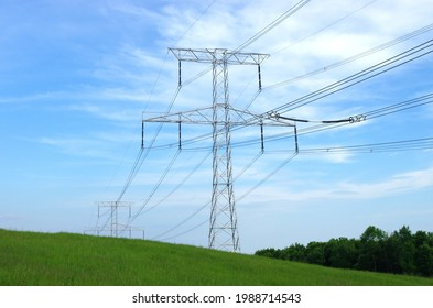 High voltage eletrical towers and lines with blue sky and green meadow. Eletricity towers on a green field. High-voltage transmission lines. Electricity transmission towers.