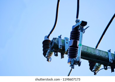 High voltage fuse on a power pole with blue sky