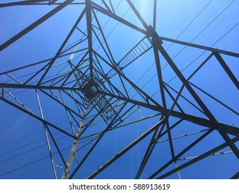 High voltage Lattice steel tower from the bottom up view with flare from sun light.