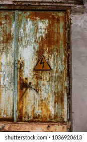 High voltage lightning sign in yellow triangle on rusty metal door, grunge abstract background. Old triangular sign Dangerously high voltage on a rusty metal background of an iron old door
