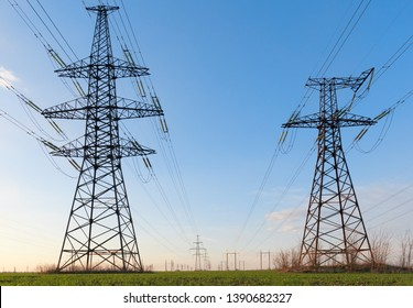 High voltage lines and power poles and green agricultural landscape during sunrise. Association of agriculture and industry in one photo. Beautiful spring landscape of the European plain.