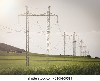 High voltage lines and power pylons in a spring agricultural landscape at sunset