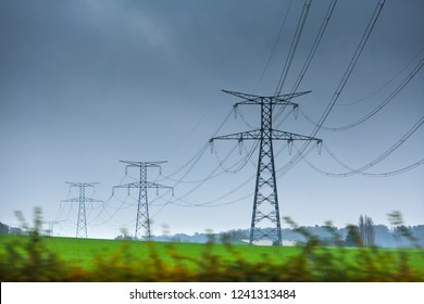 High voltage lines and power pylons in a green agricultural landscape at rainy day with.