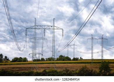 High voltage lines and power pylons in a  agricultural landscape on a heavy clouds in the  sky.