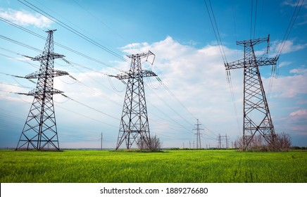 High voltage lines and power pylons in a flat and green agricultural landscape on a sunny day with clouds in the blue sky. Cloudy and rainy. Wheat is growing