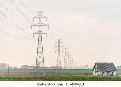 High voltage overhead power line, power pylon, steel lattice tower standing in the field near a house. The part of electricity distribution system. Sky as a background.