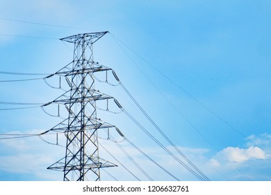 High voltage pole and wire with blue sky and clouds.