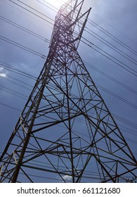 High Voltage Poles on blue sky and sunlight. Silhouette of High Voltage Structure and electric wire on sky background.