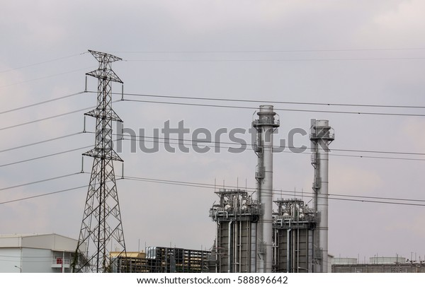 High voltage poles with Power plant on background