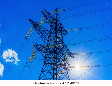 high voltage post. High-voltage tower sky background sun