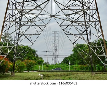 High voltage post in lines. Electricty transmission in metal structure tower over the marsh in the park. There is a car driving under the high voltage transmission lines.