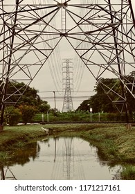 High voltage post in lines. Electricty transmission in metal structure tower over the marsh in the park.