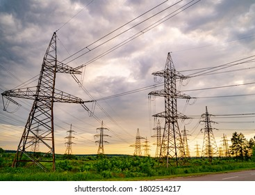High voltage post. High voltage pylons against sunset background. Energy and industrialisation concept. Selective focus