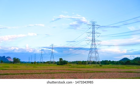 High voltage post or High voltage tower with blue sky and rice field background.