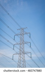 High voltage post tower with blue sky before sunset background.