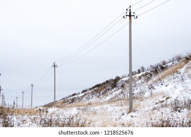 high voltage post.High-voltage tower sky background,besides the highway, line of electrical wires, winter landscape