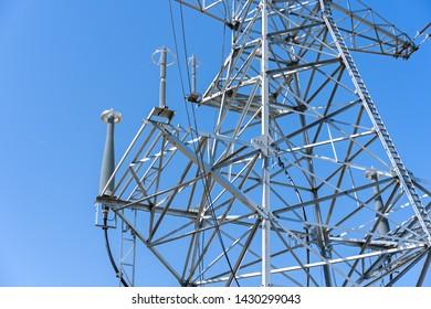 high voltage power line tower sky closeup