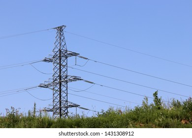 High voltage power line tower with electrical wires on blue sky background. Electricity transmission lines on a green meadow, environmental friendly power supply concept