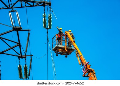 High voltage power line transmission tower workers with crane and blue sky. Hydro linemen on boom lifts working on high voltage power line towers. - Shutterstock ID 2024794652