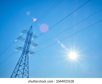 High voltage power lines on the background of blue sky with the sun