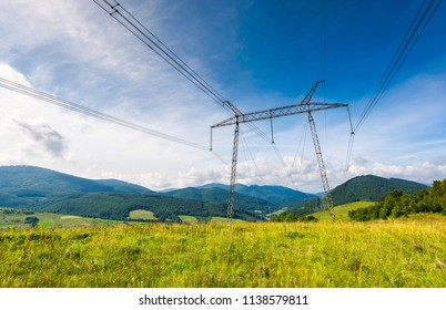 high voltage power lines tower in Carpathian mountains. lovely green energy industry concept. beautiful landscape in autumn with blue sky and some clouds