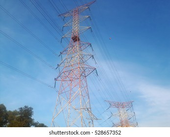 High voltage power lines tower under bright blue sky