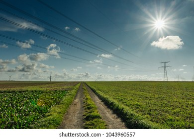 High voltage power lines and transmission towers with sunbeams in the blue sky in Normandy, France. Countryside landscape. Electricity generation and distribution. Electric power industry and nature.