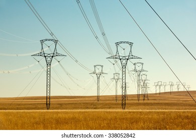 High voltage power lines and transmission towers (electric pylons) wind their way across the grassy plains on a sunny day.