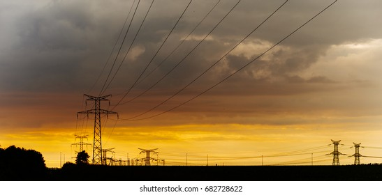 High voltage power lines and transmission towers at sunset. Poles and overhead power lines silhouettes in the dusk. Electricity generation and distribution. Electric power industry and nature concept