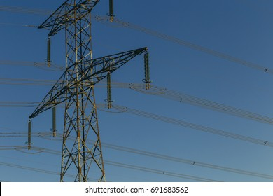 High voltage power lines and transmission towers on a bright sunny day in Normandy, France. Electricity generation and distribution. Electric power industry concept. Close up