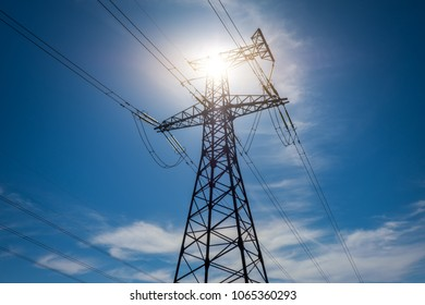 A high voltage power pylons against blue cloudy sky