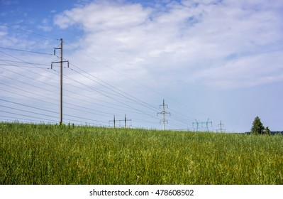 High voltage power pylons against blue sky with clouds and green forest on sunset. High voltage power towers against blue sky with clouds and green forest on sunset