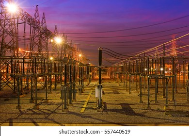 High voltage power station with lighting at night.