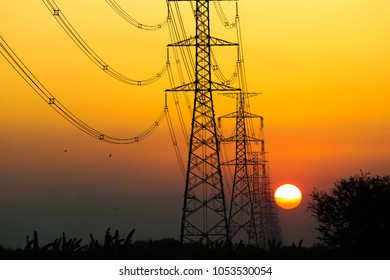 High voltage power tower close up on the worm tone sky before sunset.