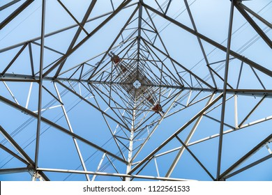 high voltage pylon on blue sky background, upward view of transmission line tower.