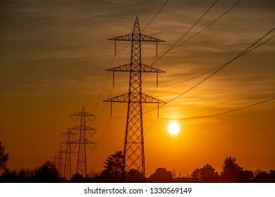 high voltage pylons against the light at sunset