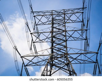 High voltage tower against blue sky background.
