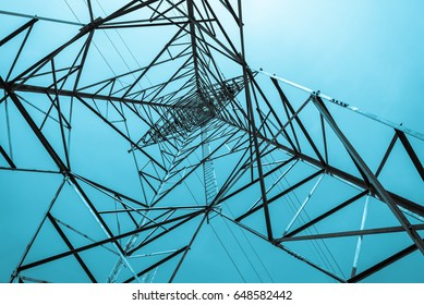High voltage tower with blue sky background at bottom view