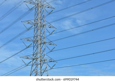 High voltage tower electricity post, with deep blue sky and cloudy. high voltage tower and electricity pylon through town silhouette against blue sky and clouds in background