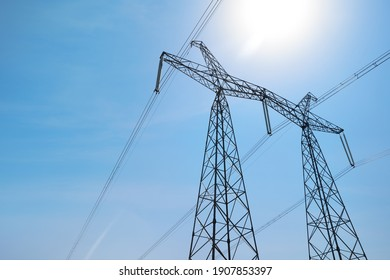 High voltage tower with electricity transmission power lines against blue sky, low angle view