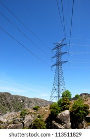 High voltage tower under blue sky and some green plants